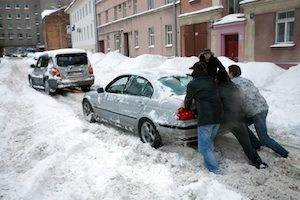 People pushing stuck car in snowy street after heavy snowfall in Riga