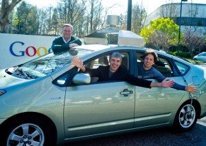 Eric Schmidt, Larry Page, and Sergey Brin pose with a Google robot car.