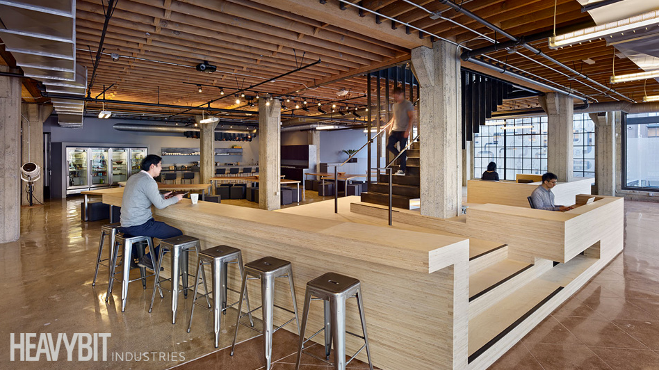 Heavybit's ground floor includes informal work areas and kitchen/cafeteria; the platform around the stairs serves as an informal dais for talks and events.