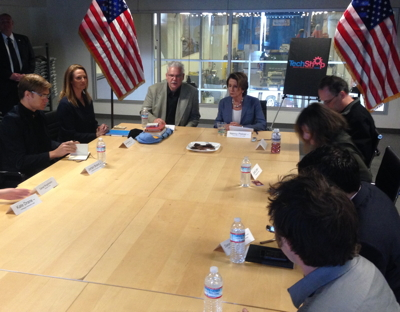Rep. Nancy Pelosi (center) flanked by TechShop CEO Mark Hatch and a group of TechShop alumni and members and local entrepreneurs.