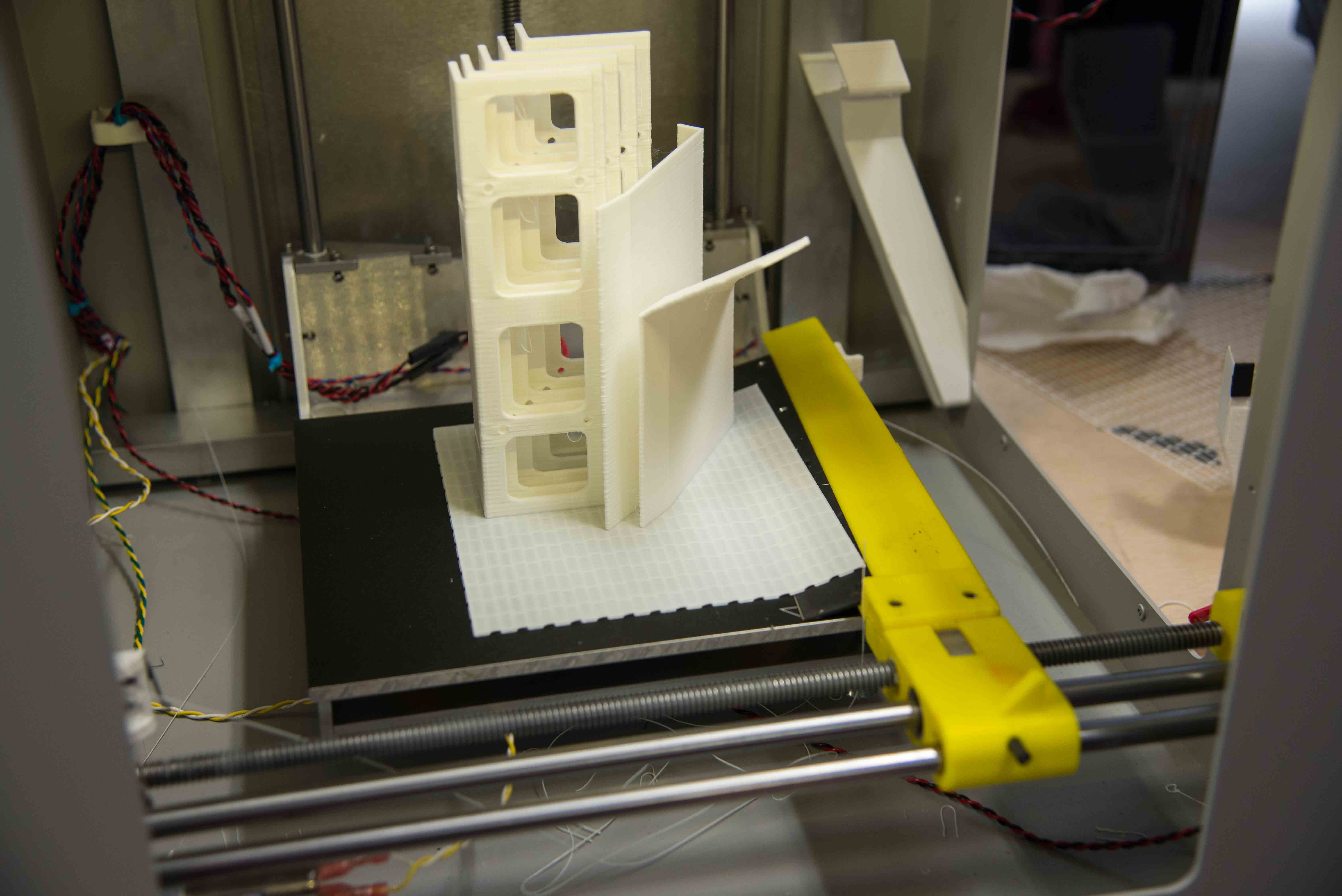 An arm cuts away 3D printed objects so the next job can run. Credit: Martin LaMonica.