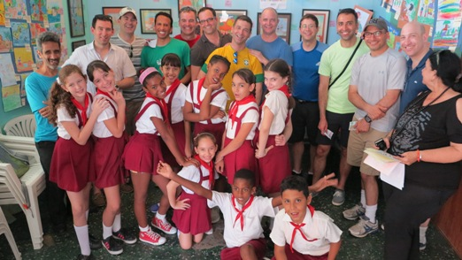 The author, center, in yellow, and fellow travelers at a Cuban school. Photo courtesy of Matt Bencke