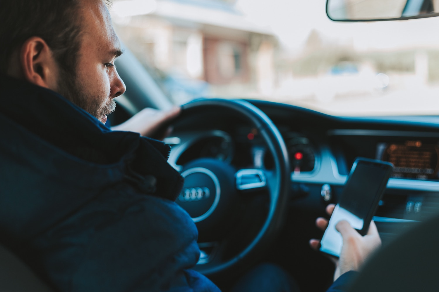 Person using smartphone in car