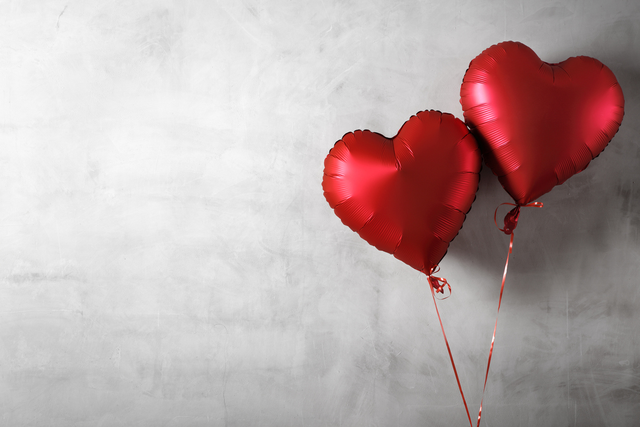 Two heart shaped foil balloons on concrete wall background