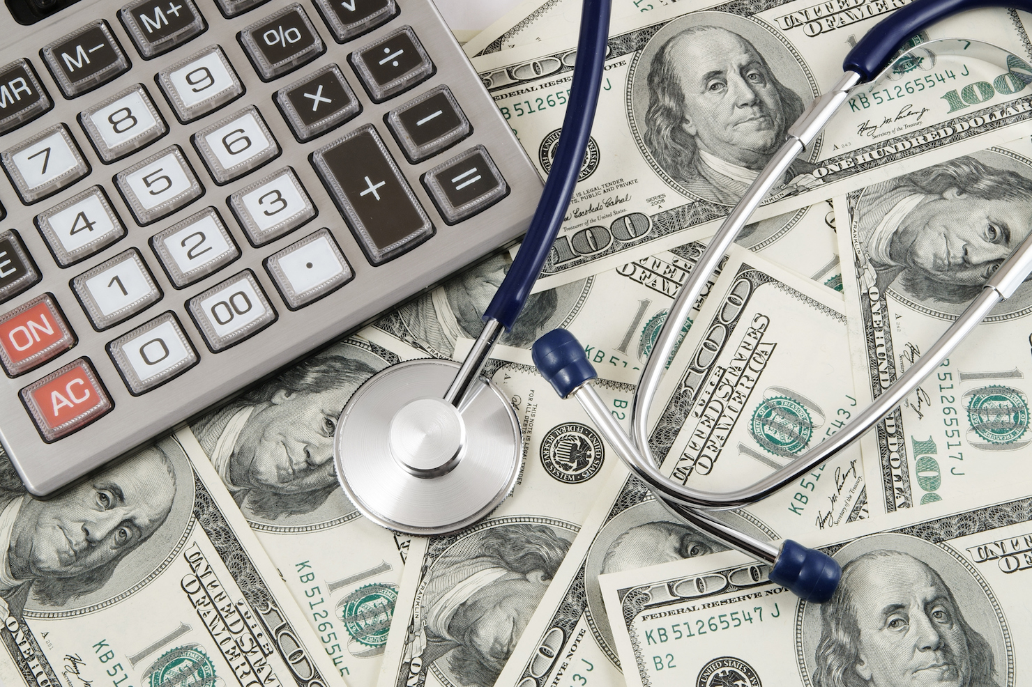 Calculator and stethoscope on banknotes background
