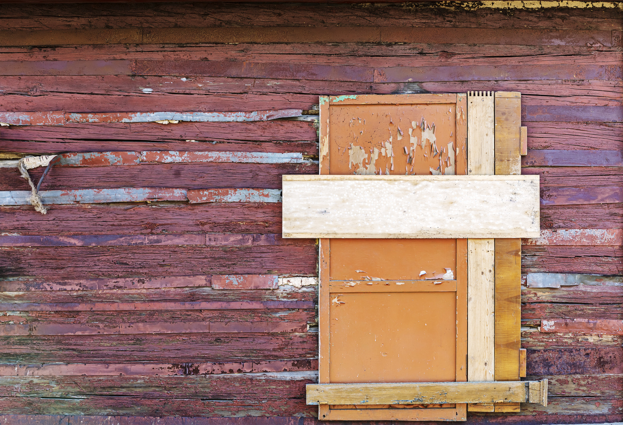 boarded up window on wooden wall of abandoned house
