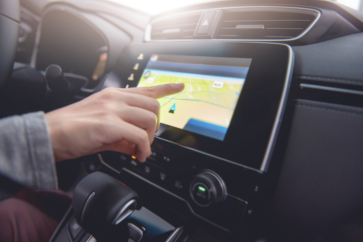 Hand using GPS navigation system in car while travel.