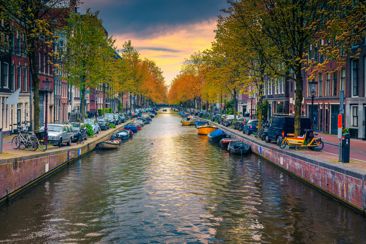 Narrow water canal with boats at sunset in Amsterdam, Netherlands